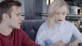 La giovane coppia sta chiacchierando mentre si sedeva alla tavola in ristorante archivi video