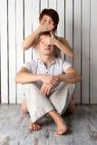 La giovane coppia sta giocando vicino alla parete di legno bianca Immagini Stock