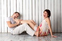 La giovane coppia sta mordendo vicino alla parete di legno bianca Immagine Stock Libera da Diritti
