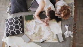 La giovane coppia sta progettando la vacanza che discute e che indica i posti per la visita su una mappa facendo uso dei perni de stock footage