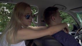 La giovane coppia sta riposando nell'uomo dell'automobile e la donna che si siede insieme dentro le coppie d'ascolto di musica de stock footage
