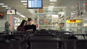 La giovane coppia sta sedendosi nel rifugio dell'aeroporto archivi video