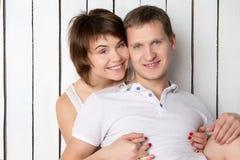 La giovane coppia sta sedendosi vicino alla parete di legno bianca Fotografie Stock