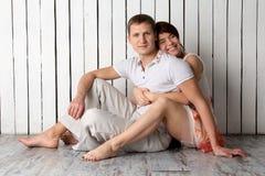 La giovane coppia sta sedendosi vicino alla parete di legno bianca Immagine Stock