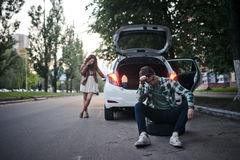 La giovane coppia sulla strada ha problemi con l'automobile Fotografia Stock Libera da Diritti