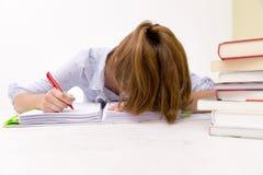 La giovane donna è caduto addormentato mentre studiava e leggendo in una biblioteca Fotografia Stock