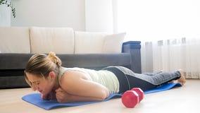 La giovane donna è caduto sul pavimento dopo avere fatto l'esercizio della plancia Immagine Stock Libera da Diritti