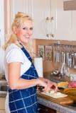 La giovane donna è cucinante e tagliante le cipolle a pezzi Immagini Stock Libere da Diritti