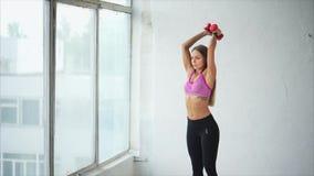 La giovane donna è impegnata nei muscoli della parte posteriore e delle mani nel club di forma fisica stock footage