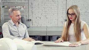La giovane donna è parlante e discutente con l'uomo adulto circa lavoro di collaborazione di progettazione archivi video