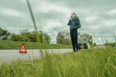 La giovane donna è sul telefono con una ripartizione dell'automobile immagine stock libera da diritti