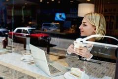 La giovane donna è telefono delle cellule di tenuta durante il resto in caffè comodo Fotografia Stock Libera da Diritti