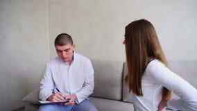 La giovane donna è venuto a vedere medico che ascolta e scrive Tipo e donna che si siedono nell'ufficio medico sullo strato sul f archivi video