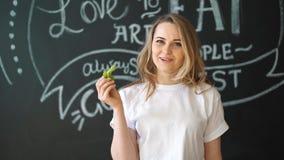 La giovane donna abbastanza allegra che posa con la lattuga verde fresca va Concetto sano di cibo stare video d archivio