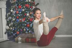 La giovane donna abbastanza flessibile sta facendo gli sport vicino all'albero di Natale, gli sport ed il concetto di festa fotografie stock libere da diritti
