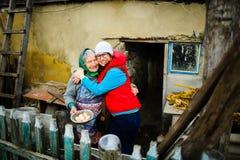La giovane donna abbraccia la donna anziana Immagine Stock