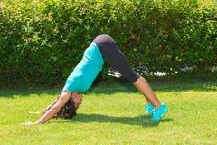 La giovane donna in abiti sportivi esegue un allungamento Fotografia Stock Libera da Diritti