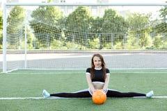 La giovane donna in abiti sportivi si siede su una cordicella Fotografia Stock Libera da Diritti