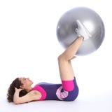 La giovane donna adatta alza la sfera di esercitazione con i piedini Immagine Stock
