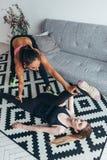 La giovane donna adatta che fa l'allungamento si esercita con l'aiuto dell'istruttore personale a casa Fotografia Stock
