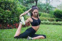 La giovane donna adatta si è vestita in abiti sportivi neri che fanno allungando l'esercizio per le gambe che si siedono sull'erb Fotografia Stock Libera da Diritti