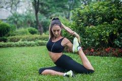 La giovane donna adatta si è vestita in abiti sportivi neri che fanno allungando l'esercizio per le gambe che si siedono sull'erb Fotografie Stock Libere da Diritti
