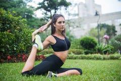 La giovane donna adatta si è vestita in abiti sportivi neri che fanno allungando l'esercizio per le gambe che si siedono sull'erb Immagine Stock Libera da Diritti