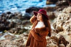 La giovane donna adorabile allegra in cappello di feltro marrone rossiccio e copre il cappotto che sta e che ride sul pilastro in Fotografia Stock