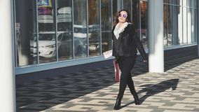 La giovane donna adorabile gira intorno la tenuta dei sacchetti della spesa sul fondo della finestra stock footage