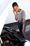 La giovane donna africana turbata che fa una pausa l'automobile ripartita ha parcheggiato dal lato di una strada e del richiedere fotografia stock libera da diritti