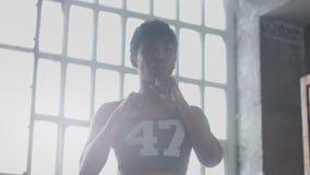 La giovane donna afroamericana della corsa mista fa un allenamento di pugilato in sottotetto soleggiato Fotografia Stock Libera da Diritti
