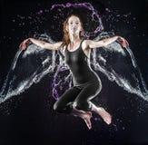 La giovane donna alata di galleggiamento in acqua spruzza Fotografia Stock