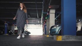 La giovane donna alla moda chiude l'automobile e va su un parcheggio archivi video
