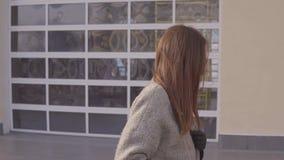 La giovane donna alla moda fa una passeggiata in una città della molla stock footage