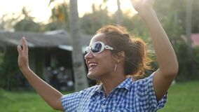 La giovane donna alla moda felice in occhiali da sole che ballano al sole canta la canzone fra le palme tropicali in giungla Movi video d archivio