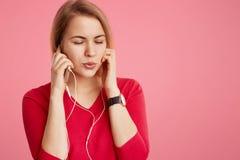 La giovane donna alla moda utilizza il telefono cellulare moderno e le cuffie da ascoltare la sua musica o pista favorita dalla l Immagini Stock Libere da Diritti