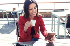 La giovane donna allegra che beve il latte del tè verde di Matcha mentre manda un sms a con il suo telefono cellulare sopra wodde immagini stock