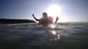 La giovane donna allegra che si rilassa sul materasso gonfiabile in mare che spruzza l'acqua si diverte nel tempo di vacanza Movi stock footage