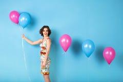La giovane donna allegra con elio balloons su un fondo blu fotografia stock libera da diritti