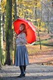 La giovane donna allegra costa con un ombrello rosso nel parco di autunno Immagini Stock