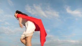 La giovane donna allegra gioca in eroe eccellente funzionamento e risata felici della ragazza del supereroe in mantello rosso, ma archivi video