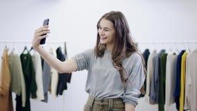 La giovane donna allegra prende le foto se stessa sulla macchina fotografica dello smartphone in una stanza dell'abbigliamento archivi video
