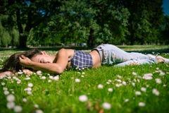 La giovane donna allegra si trova su erba verde immagini stock libere da diritti
