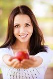 La giovane donna allunga la mela Immagine Stock Libera da Diritti