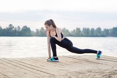 La giovane donna allunga le sue gambe durante gli esercizi di allenamento di addestramento Fotografie Stock Libere da Diritti