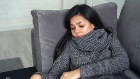 La giovane donna alta vicina misura la temperatura che si siede sul sofà nella casa Sensibilità della donna infelice durante un v video d archivio