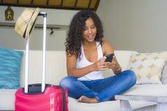 La giovane donna americana dell'africano nero attraente e felice a casa con la valigia facendo uso del telefono cellulare che va  fotografie stock libere da diritti