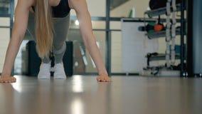 La giovane donna americana sta facendo spinta-UPS sul pavimento al club di sport stock footage