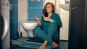 La giovane donna arrabbiata in pigiami getta il test di gravidanza ed il gabinetto rilegato in bagno video d archivio