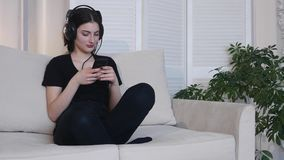 La giovane donna ascolta musica che si siede sul sofà a casa 4K video d archivio